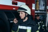 Fotografie ženské hasič na přenosné rádio s kolegou za na hasičské stanici