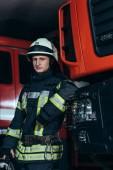 portrét hasič v uniformě a helmu, opíraje se o vůz na hasičské stanici