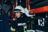 portrét ženy hasič v ochranné jednotné mluví do přenosné rádio na požární stanici