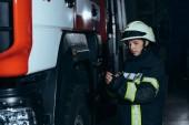 Fotografie ženské hasič v helmě kontrola ochranné uniformu na hasičské stanici