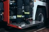 Fotografie částečný pohled hasič v ohnivzdorné jednotné postavení na vozíku na požární stanici