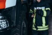 Fotografie Oříznout záběr ženské hasič v ochranné uniformě s přenosným rádiem na hasiče