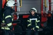 Hasiči v ohnivzdorné uniformu a přilby bavit na hasičské stanici