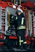 hasič v ochranné uniformě a přilbu při pohledu kamery na hasičské stanici