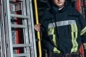 Oříznout záběr hasič v ochranné uniformě na hasičské stanici