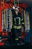 fireman in protective uniform and helmet standing on truck at fire station