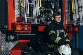 portrét mužské hasič s ochrannou helmou v rukou v kamionu na hasiče