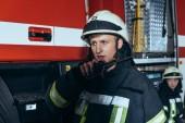 Fotografie Selektivní fokus hasič v jednotné mluví na přenosné rádio s kolegou za na hasičské stanici