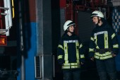 Fotografie usmívající se Hasiči v ochranných uniformu a přileb na sebe dívali na hasičské stanici