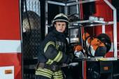 portrét hasič v helma stojí u kamionu na hasičské stanici
