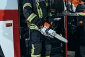 částečný pohled hasič v držení elektrické ochranné uniformě viděl v rukou na hasičské stanici
