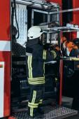 Fotografie boční pohled na ženské hasič stojící na zařízení v autě na hasiče