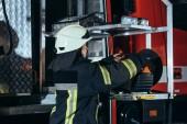 boční pohled na ženské hasič stojící na zařízení v autě na hasičské stanici