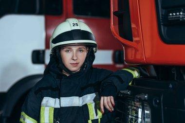 Portrait of female firefighter in helmet leaning on truck at fire station stock vector