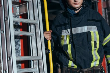 cropped shot of fireman in protective uniform at fire station