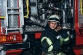 portrét hasič kontrola ochranné helmy v kamionu na hasičské stanici