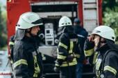Fotografie Selektivní fokus hasičů bavit při brigádě v hasičské auto na ulici