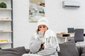 freezed young woman in warm clothes with runny nose sitting on couch at home