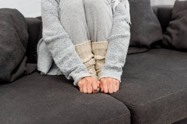 cropped shot of freezed woman in warm clothes sitting on couch and warming her feet