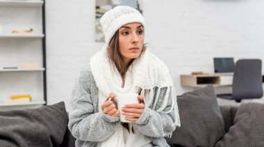 Freezed young woman in warm clothes holding cup of warming tea while sitting on couch at home stock vector