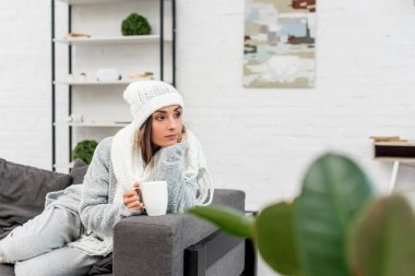 Thoughtful young woman in warm clothes holding cup of hot tea and looking away while sitting on couch stock vector