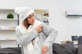 Fotografie mrznout mladá žena dát na teplé oblečení s klimatizací na pozadí