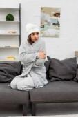 mrznout mladá žena v teplé oblečení sedí na gauči doma