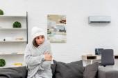 Fotografie mrznout mladá žena v teplé oblečení sedí na gauči doma s klimatizací na pozadí
