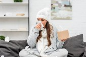 diseased young woman in warm clothes sitting on messy couch and sneezing with paper napkins at home