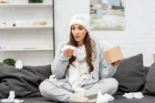 Kranke junge Frau in warmer Kleidung sitzt auf schmuddeliger Couch und niest zu Hause mit Papierservietten