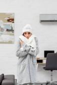 Fotografie zmrazení mladá žena v teplé oblečení s klimatizaci na pozadí