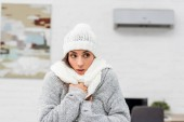 Fotografie close-up portrait of freezing young woman in warm clothes with air conditioner on background