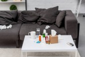 Photo table with various medicines and couch at living room