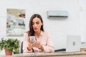 Fotografie attraktive junge Geschäftsfrau nutzt Smartphone bei der Arbeit im Büro