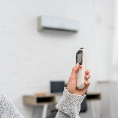 Cropped shot of woman in sweater holding air conditioner remote control stock vector