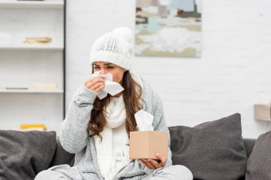 sick young woman in warm clothes blowing nose with paper napkin at home