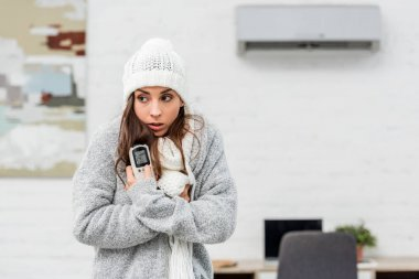 freezing young woman in warm clothes holding remote control with air conditioner on background