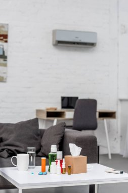 table with various medicines at living room with workplace on background