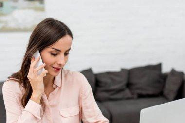 telefonla konuşurken ve laptop ile ofiste çalışan güzel genç iş kadını