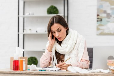 sick young businesswoman trying to work while suffering from headache at workplace