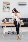 sick young businesswoman n scarf leaning back at workplace in office