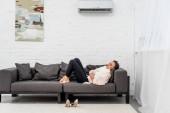 boční pohled na nemocné mladé ženy v šátek ležet na gauči pod klimatizace doma