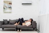 boční pohled na nemocné mladé ženy leží na gauči doma
