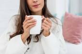 oříznutý snímek mladé ženy držící šálek kávy