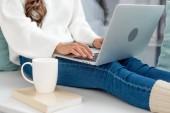 Oříznout záběr na volné noze s šálkem kávy práci s notebookem na parapetu doma
