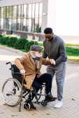 young african american nurse helping senior disabled man to get up from wheelchair on street