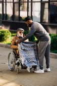 african american nurse covering senior disabled man in wheelchair with plaid on street