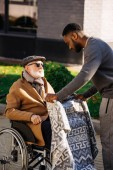 african american man covering senior disabled man in wheelchair with plaid on street