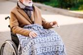 Fotografie Erschossener Senior im Rollstuhl mit Plaid an Beinen auf Straße