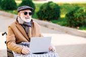 Glückliche Seniorin im Rollstuhl mit Laptop auf der Straße